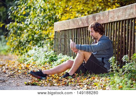Young handsome runner with smart phone with earphones resting, listening music, sitting on a bridge