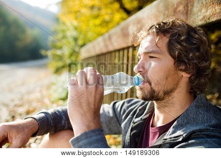 Young handsome runner with water bottle sitting on a bridge, drinking, resting