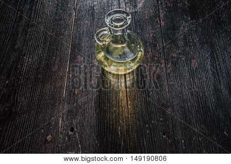 Glass jar of vegetable oil on the dark wooden table