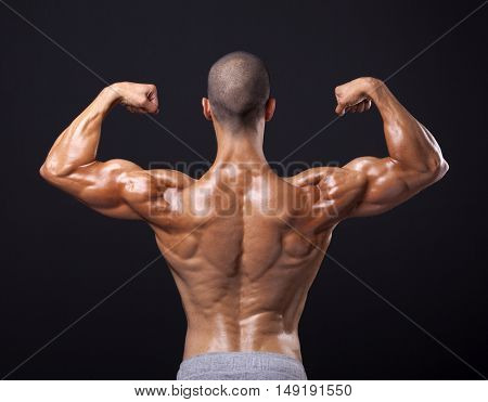 Back view of a male bodybuilder flexing his biceps on black background