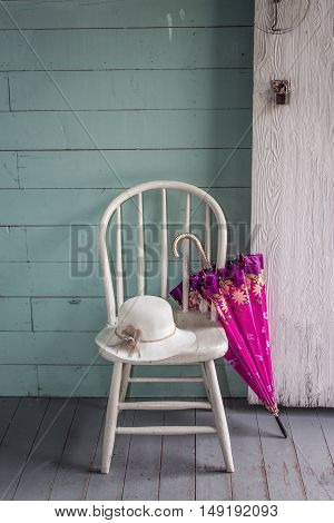 vertical image of a vintage interior blue plank wall and a white painted chair sitting on a grey plank floor with a vintage hat sitting on the chair and a pink coloured umbrella leaning against it.