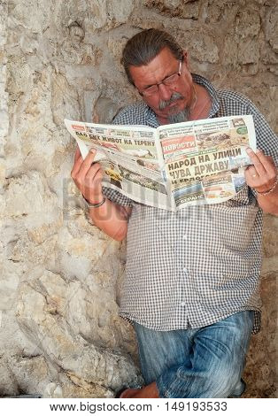 HERCEG NOVI, MONTENEGRO - JULY 21, 2016: man reading newspaper printed in Cyrillic characters against stone wall