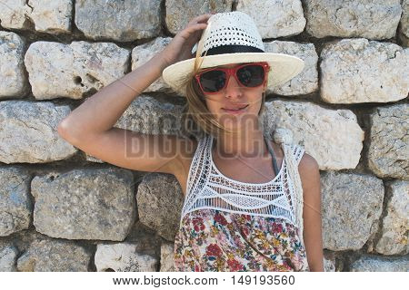 Young woman posing against stone wall on vacation