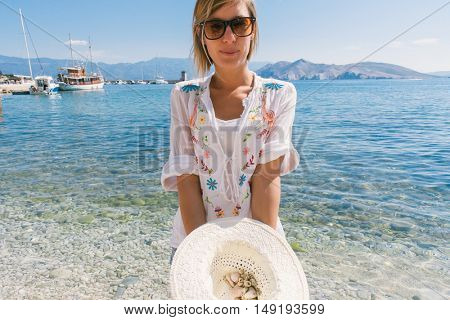 Young happy woman picking shells on the beach