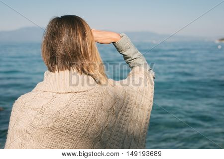Woman looking away by the sea. Autumn vacation concept.