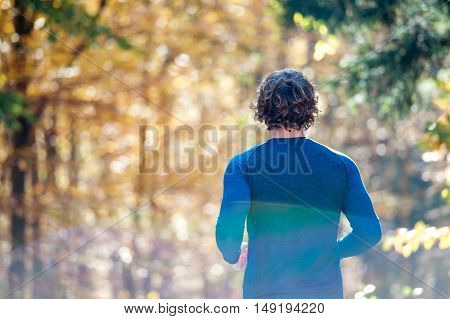Young handsome runner outside in sunny autumn nature, rear view