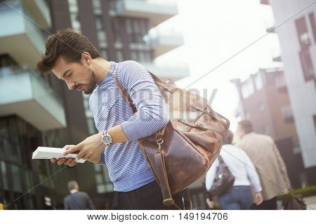 Man standing outdoors absorbed by an interesting book