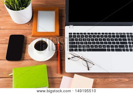 Still life photo of laptop, notepad, coffee, glasses and other items on wooden table.