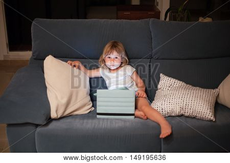 Child Sitting In Sofa With Tablet Looking