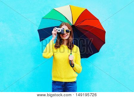 Happy Smiling Young Woman With Vintage Camera Holding Colorful Umbrella In Autumn Day Over Blue Back