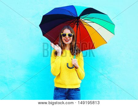 Pretty Young Woman Shocked With Colorful Umbrella In Autumn Day Over Blue Background Wearing Yellow