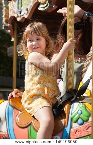 portrait of three years old blonde pretty girl with yellow dress sitting on a colorful horses in a carousel next to brunette woman mother smiling
