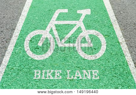 Closeup white painted of bicycle sign in green bike lane at the street floor in park textured background