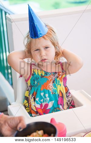 two years old blonde child with bright blue cardboard party hat sitting in white high chair looking seriously