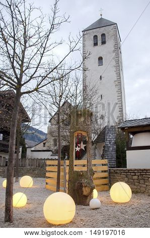 Brunico Italy 14 December 2014: christmas decorations in the San Candido village in Alpa Pusteria region. In the background the white tower of San Candido