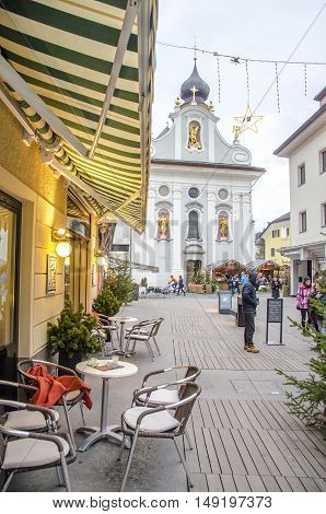 Brunico Italy 14 December 2014: A bistro chairs with the church of San Candido in the background during winter holidays