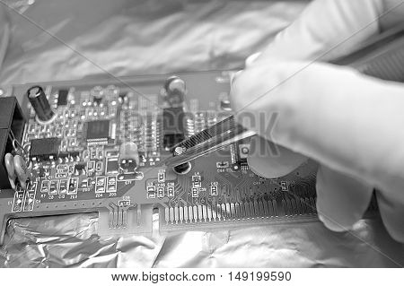 Electronic technician repairing computer hardware in the lab