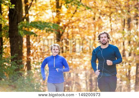 Beautiful couple running together outside in sunny autumn forest