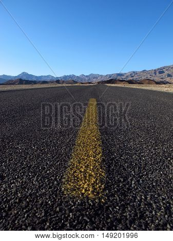 Close up of a bitumen road through Death Valley in the Sierra Nevada, California, and Nevada. Light, natural colors.