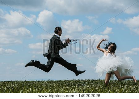 Happy bride and handsome groom elegant fashion married couple in wedding dress suit jump and take photos on beautiful field on blue sky