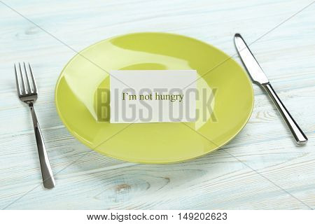 Green plate on a blue wooden table, i am not hungry