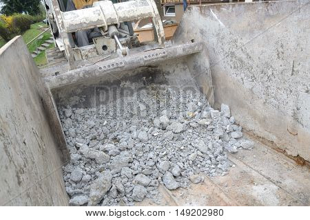 building rubble is poured by excavators in collection containers