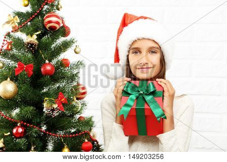 Young Girl In Santa Claus Hat With Gift Box Near Fir-tree