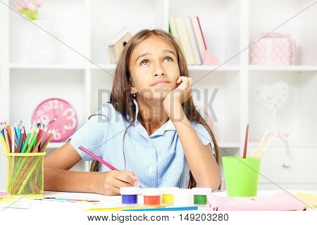 Little girl sitting and drawing at home