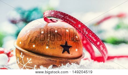 Christmas balls jingle bells. Red ribbon with text Happy Christmas. Snowy abstract background and decoration.