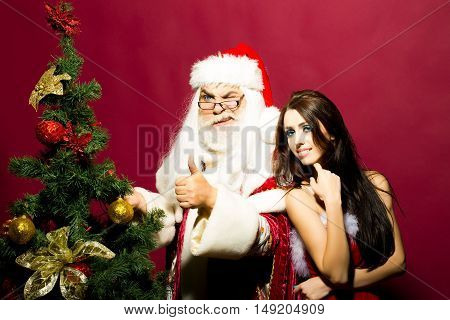 Santa claus man gives thumbs up gesture with pretty girl with long brunette hair in red dress near Christmas tree