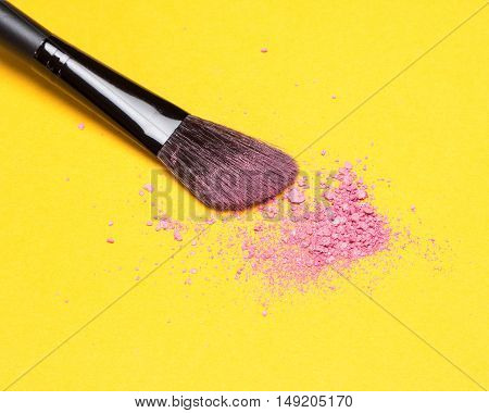 Close-up of makeup brush with crushed shimmer blush pink color on bright yellow background