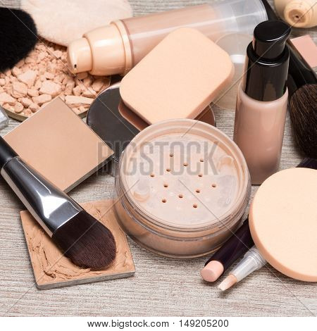 Makeup products and accessories to even out skin tone and complexion. Concealers, bottles of liquid foundation, loose and compact powder, makeup brushes and cosmetic sponges on shabby wooden surface