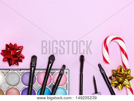 Christmas makeup cosmetics. Bright color glitter eyeshadow, black eyeliner, mascara, red lip gloss, make up brushes and applicator with candy cane and gift wrap bows on pink background. Copy space