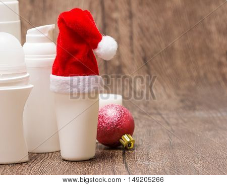 Christmas skincare cosmetics. Close-up of various cosmetic products for face and body care with Santa hat and Christmas ball on wooden surface. Copy space. Christmas sale or gift concept