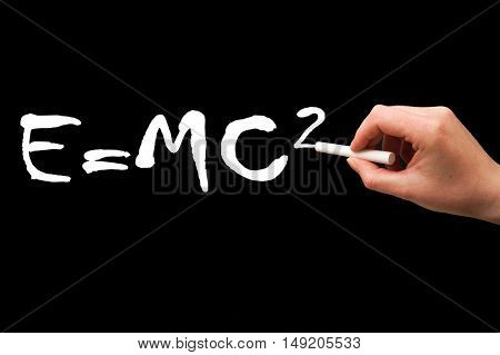 Right hand writing on a blackboard in white mass-energy eguivalence