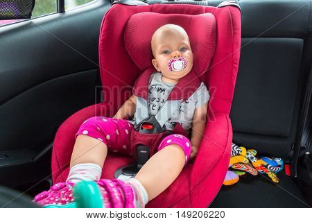 Cute baby girl is seating in the car on child safety seat