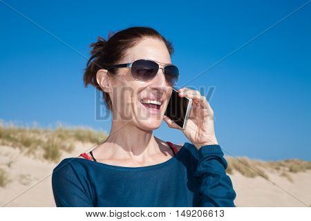 Blue Sweater Woman With Sunglasses Talking On Mobile
