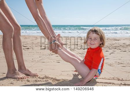 Funny Child Slipping By Woman On Sand Beach