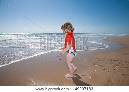 two years old blonde child with orange surf shirt and swimsuit walking on golden sand beach to the ocean