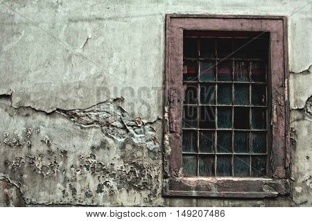 Old dirty window on old cracked wall