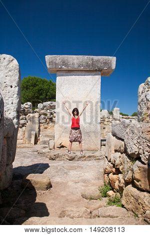 Woman Greeting In Prehistoric Taula In Minorca Island