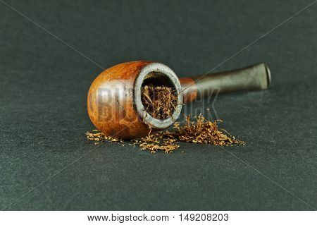 Old smoking pipe and tobacco on dark background