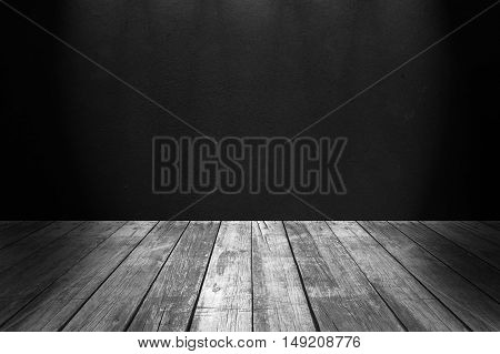 Black concrete wall an wooden floor illuminated from above empty interior
