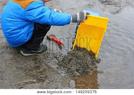 Children's outdoor play. Child in a blue jacket boots gloves hat and black pants plays with toy machine near a huge swollen after rain puddles.