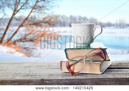 Coffee, tea or hot cocoa chocolate cup on books with eyeglasses outdoors in winter. Pile of books, glasses and white coffee cup in nature.