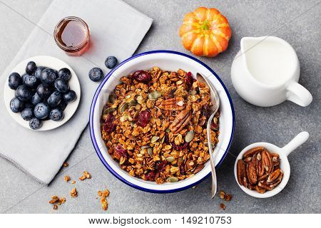 Healthy breakfast. Fresh granola, muesli with pumpkin seeds, pecan nuts and maple syrup in white bowl. Top view. Copy space