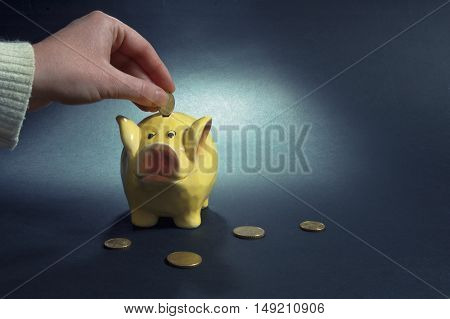 Female hand putting coin into yellow piggy coin bank.