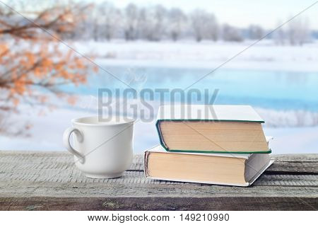 Hot coffee, tea or hot cocoa chocolate cup with books outdoors in winter. Pile of books, and white coffee cup in nature.