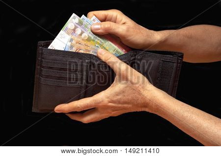 Black wallet with money in hands. Swiss francs banknotes.