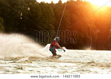 Wakeboarder surfing across a lake on sunset